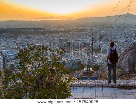 Athens, Greece - October 15, 2016: Man looking Athens skyline and sunset from Lykavittos hill, Athens, Greece