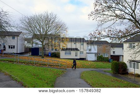 Bracknell,England - November 22, 2016: A pedestrian passes in front of homes on an English housing estate in Bracknell, England on a wet afternoon in November