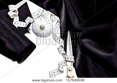 Top view accessories for sewing lie on a white background. Black satin fabric roll, measuring tape, scissors, needles. Fashion, Design Studio tailoring, atelier concept. Desk of worker.