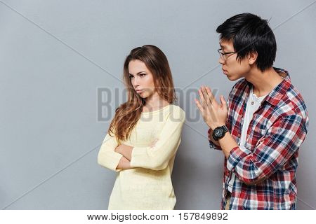 Young asian man asking for forgiveness his upset girlfriend isolated on the gray background