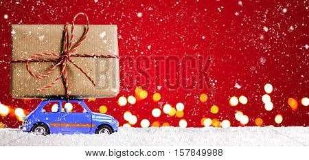 Blue retro toy car delivering Christmas or New Year gifts on festive red background
