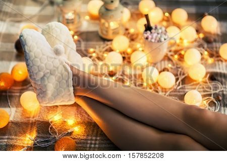 Woman feet in woollen socks and cup of hot chocolate. relax holidays concept