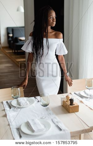 Sexy black woman in an elegante white evening dress is standing in restaurant of a luxury hotel. Girl puts her hands on the chairs and looking at the window.the restaurant has a modern design. Femine is standing near well decorated table.