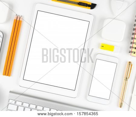 Top view on desk: Keyboard, mouse, tablet computer and smartphone on white table background with space for text and copy space.