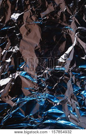 Full frame take a sheet of crumpled aluminum foil, the blue light on the side, crumpled foil, abstract background