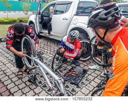 Labuan,Malaysia-Jan 1,2014:Cyclist repairing his mountain bike during participating fun ride day at Labuan.Malaysia encourage his peoples to cycling in their daily activity for good healthy.