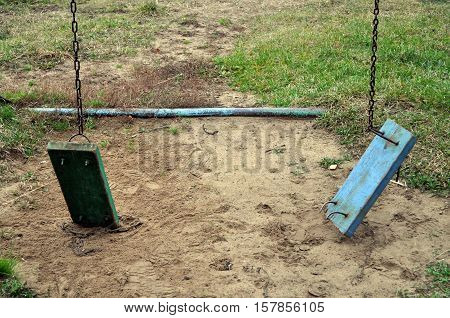 a two broken swing Forgotten the playground.