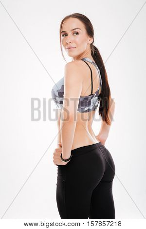 Back view of fitness woman in studio. looking at camera. isolated white background