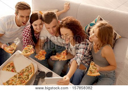 Friends taking selfie while sitting on couch and eating pizza