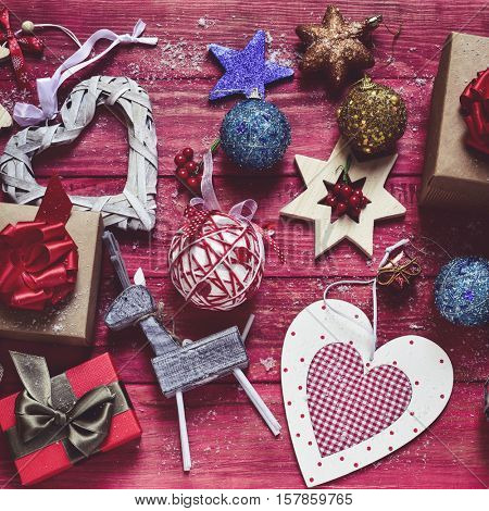 high-angle shot of some cozy rustic christmas ornaments, such as a wooden reindeer some star-shaped ornaments or some baubles, and some gifts placed on a red rustic wooden surface