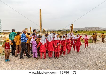 PASARGAD, IRAN - MAY 4, 2015: The group of school children with the teacher checking out the archaeological site of the old city.