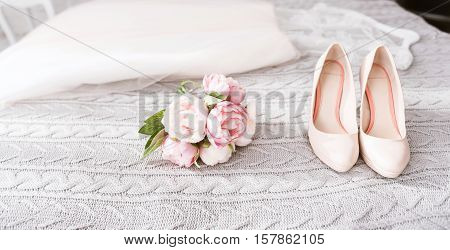 High heel shoes of the bride. White amazing stunning wedding dress and high heel shoes lying on the bed near the pink wedding bouquet in the bedroom