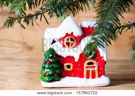 Branch christmas tree with winter house on wood background. Greeting card