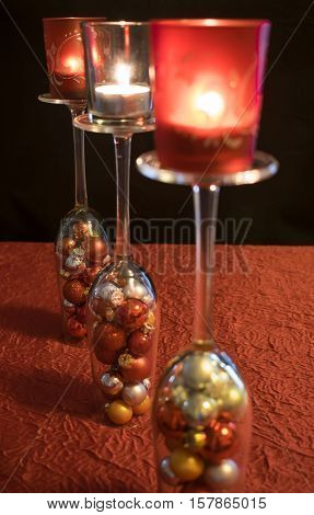 3 inverted champagne glasses filled with colorful Christmas balls on a red tablecloth. The champagne glasses are arranged in a row and carry each a candle holder with a burning candle.