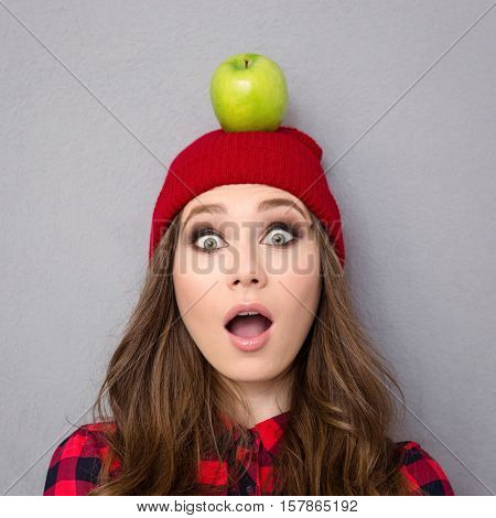 Portrait of a young woman with apple on head looking at camera over gray background