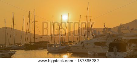 Sail boats against the sunset at Paros island in Greece.