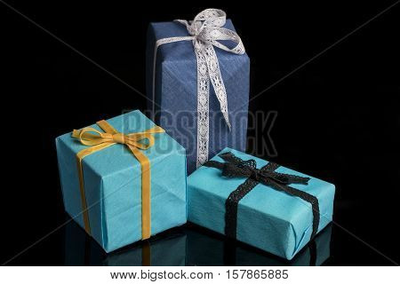 Three presents of different sizes wrapped in blue and turquoise textured paper tied with lace and velvet ribbons on black from high angle