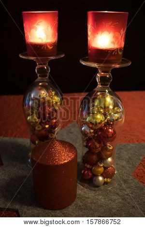 2 cocktail glasses filled with colorful Christmas balls on a gray star-shaped trivet decorated with a red candle. The cocktail glasses are turned around and carry each a red Tealight holder with a burning candle.