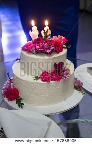 Wedding Cake With Carnations On A Glass Table