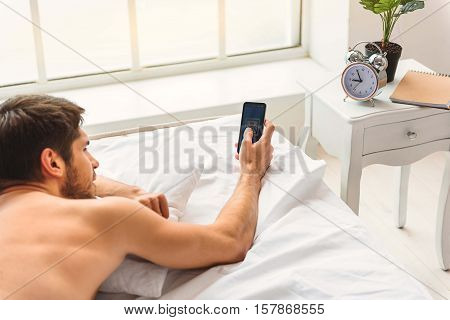 Appealing young man is checking his email after waking up. He is touching smartphone to open message with interest. Guy is lying in bed near clock