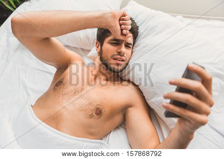 Bad news after sleep. Young man is lying in bed and looking at mobile phone with sadness. He is touching his head desperately