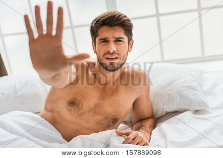Let me sleep more. Tired young man is lying in bed and stretching stop hand forward. He is looking at camera and begging