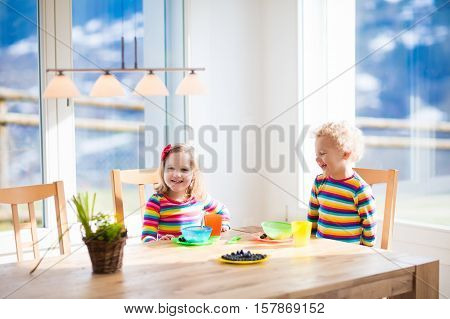 Kids Eating Breakfast At Home. Fruit And Milk For Children.