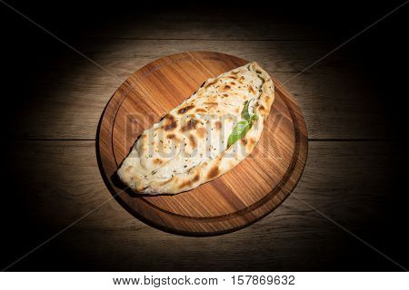 Fried thick cheburek served on a wood tray on old wooden table in dark