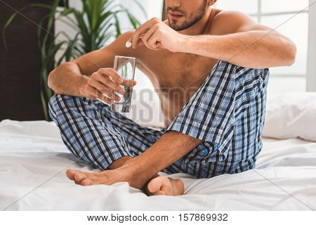 Sad young man suffers from hangover in morning. He is putting pill into glass with water while sitting on bed