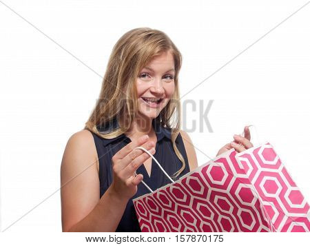 A blond woman oping a shopping bag.
