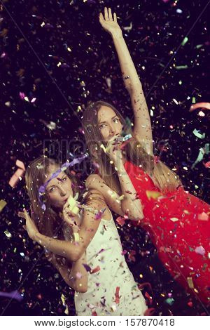 Two beautiful girls having fun at New Year's party dancing and blowing party whistles.