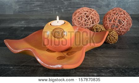 A decorative Bowl with a burning candle on a wood surface decorated with beautiful woven balls