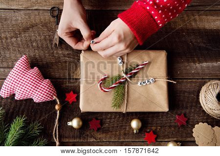 Hands of unrecognizable woman wrapping and decorating Christmas present laid on a wooden table background. Studio shot.