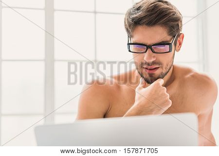 Pensive young man is using computer for work at home. He is sitting with naked torso