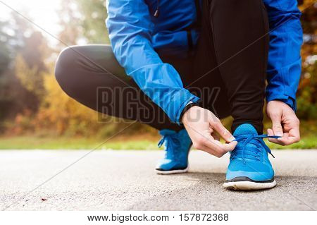 Unrecognizable runner in blue jacket outside in colorful sunny autumn nature, tying shoelaces