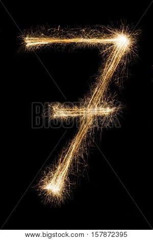 New year font made from sparkler firework on black background. Number seven. Illuminated math figure pattern