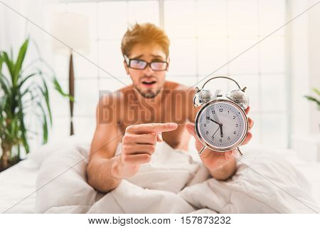 I must wake up so early. Upset young man is holding clock and pointing finger at it. He is sitting and looking at camera with sadness