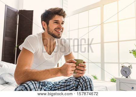There is no place like home. Carefree young man is drinking coffee and dreaming. He is sitting on bed and smiling