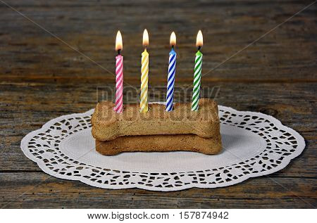 row of lit birthday candles on dog milk bone with lace paper doily