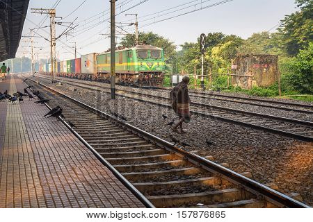 KOLKATA, INDIA - NOVEMBER 22, 2016: An unidentified old man dangerously attempts to cross the railway tracks in front of a goods train at Lake Gardens station, Kolkata.