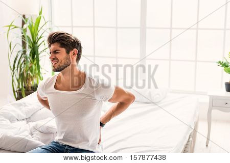 Young man suffering from backache. He is sitting on bed and touching body with frustration
