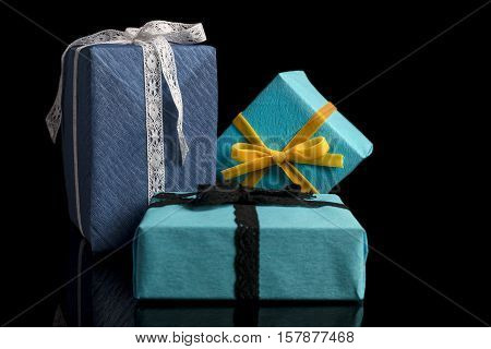 Three presents of different sizes wrapped in blue and turquoise textured paper tied with lace and velvet ribbons on black from side