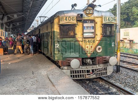 KOLKATA, INDIA - NOVEMBER 22, 2016: An intrastate morning local train boarding passengers at Lake Gardens station, Kolkata, India.