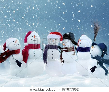 .Many snowmen standing in winter Christmas landscape.