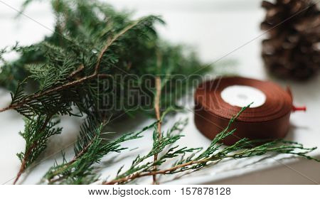 Gift wrapping closeup background. Ribbon for packaging christmas present boxes, thuja tree branches, pine cones and scissors. Christmas and winter holidays concept. Selective focus