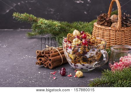 Home fresh crunchy granola with hazelnuts, dried cranberries, Christmas candy stick Santa Claus, in a transparent cup with milk on a festive breakfast in the family circle. Against the background of Christmas tree branches and Christmas red balls.