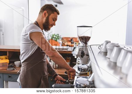 handsome worker using tamper and portafilter, side view