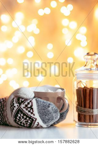 Drinking hot chocolate over led lights bokeh in cafe. Hands in gloves holding warm cup with coffee. Cinnamon sticks in glass jars. Winter mood, holiday decoration, magic Christmas.