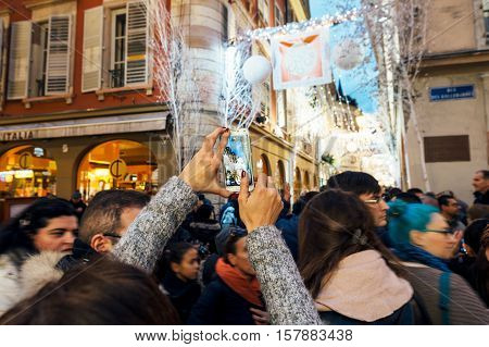 STRASBOURG FRANCE - DEC 06 2015: taking a photo of the Christmas decorations with a mobile smartphone with the magic atmosphere on the Rue Des Orfevres in central Strasbourg