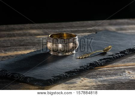 Ancient melkhiorovy saltcellar with a beautiful spoon on a black slate plate in style a rustic
